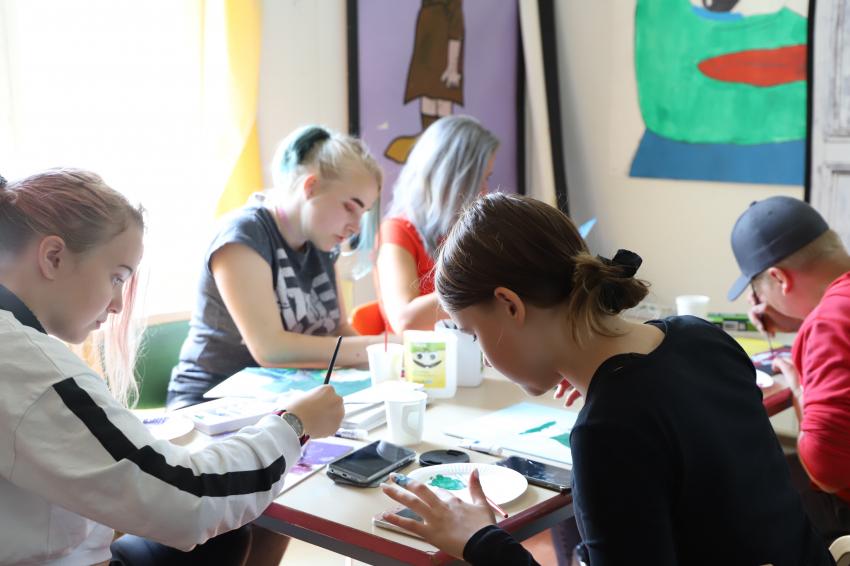 Nuoria pöydän ääressä maalaamassa